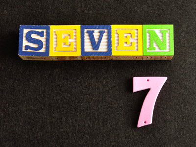 Number seven spelt out in child's blocks