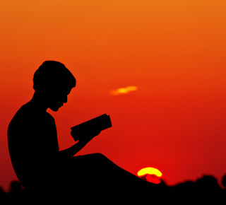 Silhouette of a boy reading at sunset