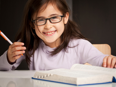 Young girl sitting at desk using a dictionary