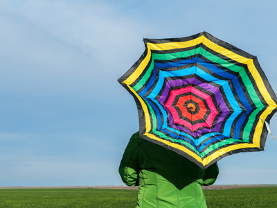 Brightly-colored umbrella against blue sky