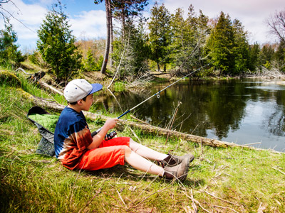 Teenage boy fishing by a river