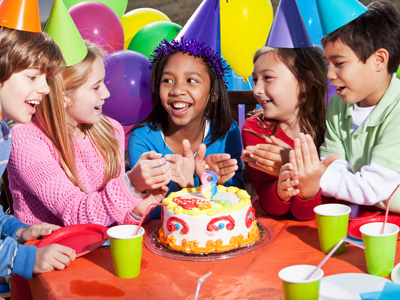 Children at birthday party with cake and balloons