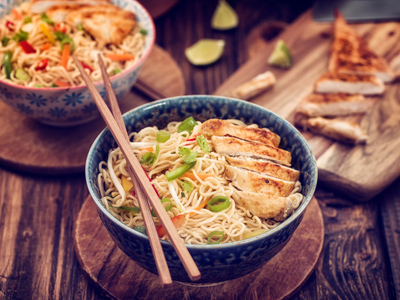 Bowl of noodles with chicken and chopsticks
