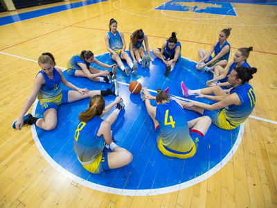 Basketball team sitting on indoor court