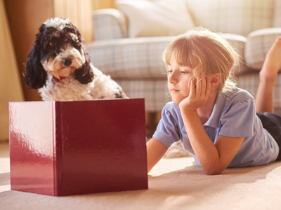 Girl and pet dog reading story book