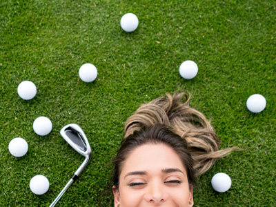 Female golfer lying on grass smiling