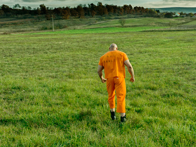 An escaped prisoner fleeing over the countryside