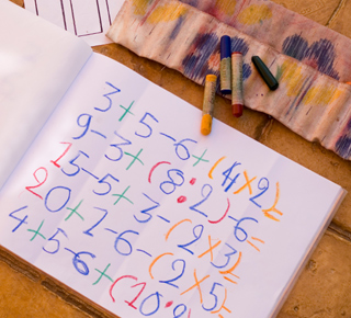 Simple maths and numbers written colourfully in a book
