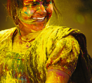 Happy girl covered in paint to illustrate diversity