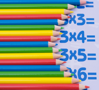 Maths tables partly concealed by pencils