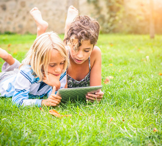 Two children lying in the grass and studying a computer tablet