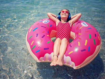 Girl on inflatable in water in the sun