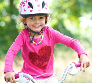 Happy little girl safely riding a bicycle