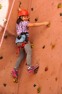 Girl climbing rock wall with confidence