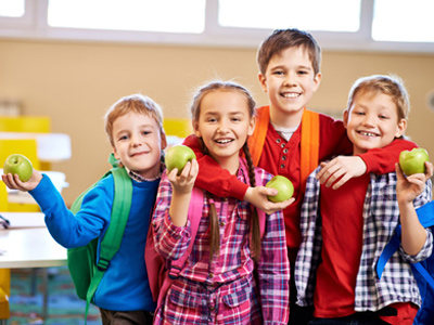 Happy primary school children, each holding an apple