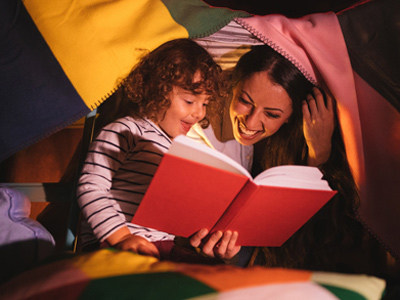 Mother and young child reading a book together
