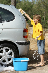 Young boy cleaning the family car