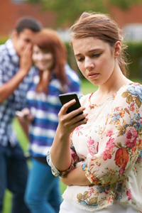 Teenagers cyberbullying another girl via her mobile phone