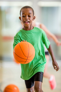 Happy young boy playing basketball