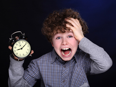 Boy holding alarm clock and realising he's late for school
