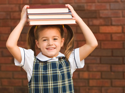 Young girl balancing school books on her head