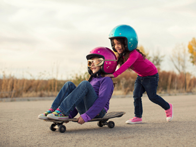 Two young friends playing on a skateboard