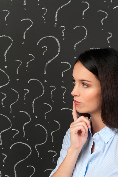 Thoughtful woman surrounded by question marks