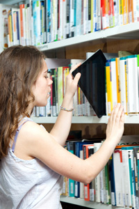Teenage girl pulling iPad from shelf of books