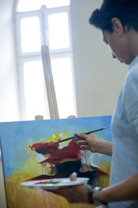 A GCSE age art student painting a picture