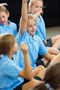 Pupils in primary school class raising their hands