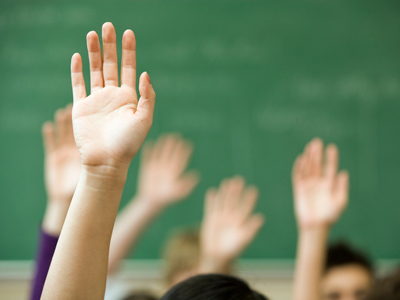 Hands raised by school pupils