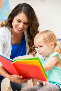 Toddler age girl reading to nursery teacher