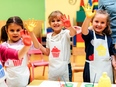 Young girls in nursery school painting with their hands