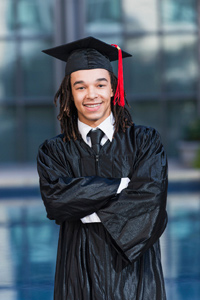 Boy of secondary school age wearing graduation gown