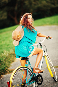 A happy teenage girl riding a bicycle