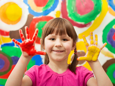 Young girl learning by playing with paint
