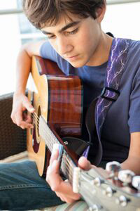 Teenage boy learning to play the guitar