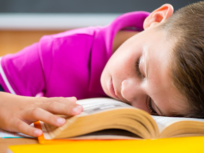 Sleeping schoolboy using textbook as a pillow