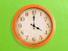 Orange clock showing 4:00 on green background