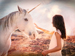 Woman stroking a unicorn with hazy background
