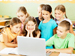 Elementary schoolchildren playing quiz on laptop