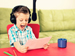 Boy reading aloud into microphone with headphones