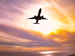 Silhouette of airplane flying in sunset sky