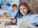 Schoolgirl with research book sitting at desk