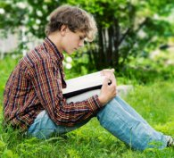 Boy sitting on grass and reading a book