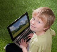Young, smiling boy using a computer
