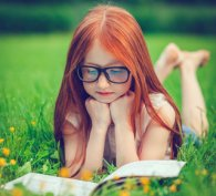 Young girl lying in the grass and reading a book