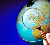 Magnifying glass examining a globe of the world