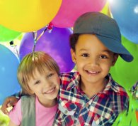 Two happy and healthy children surrounded by balloons