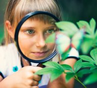 Young scientist examining a plant with a magnifying glass